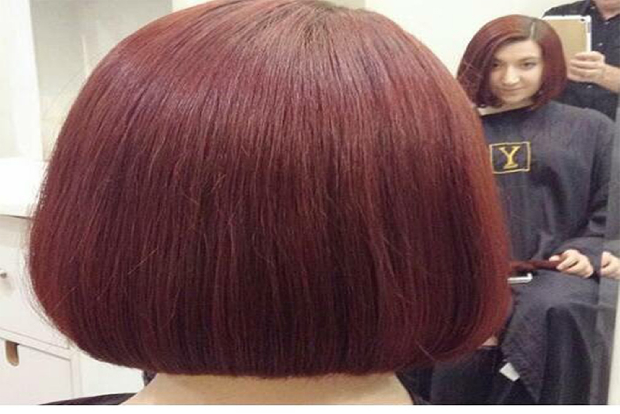 we see the back of woman's head withshiny bob, as she looks into the mirror to see her new haircut