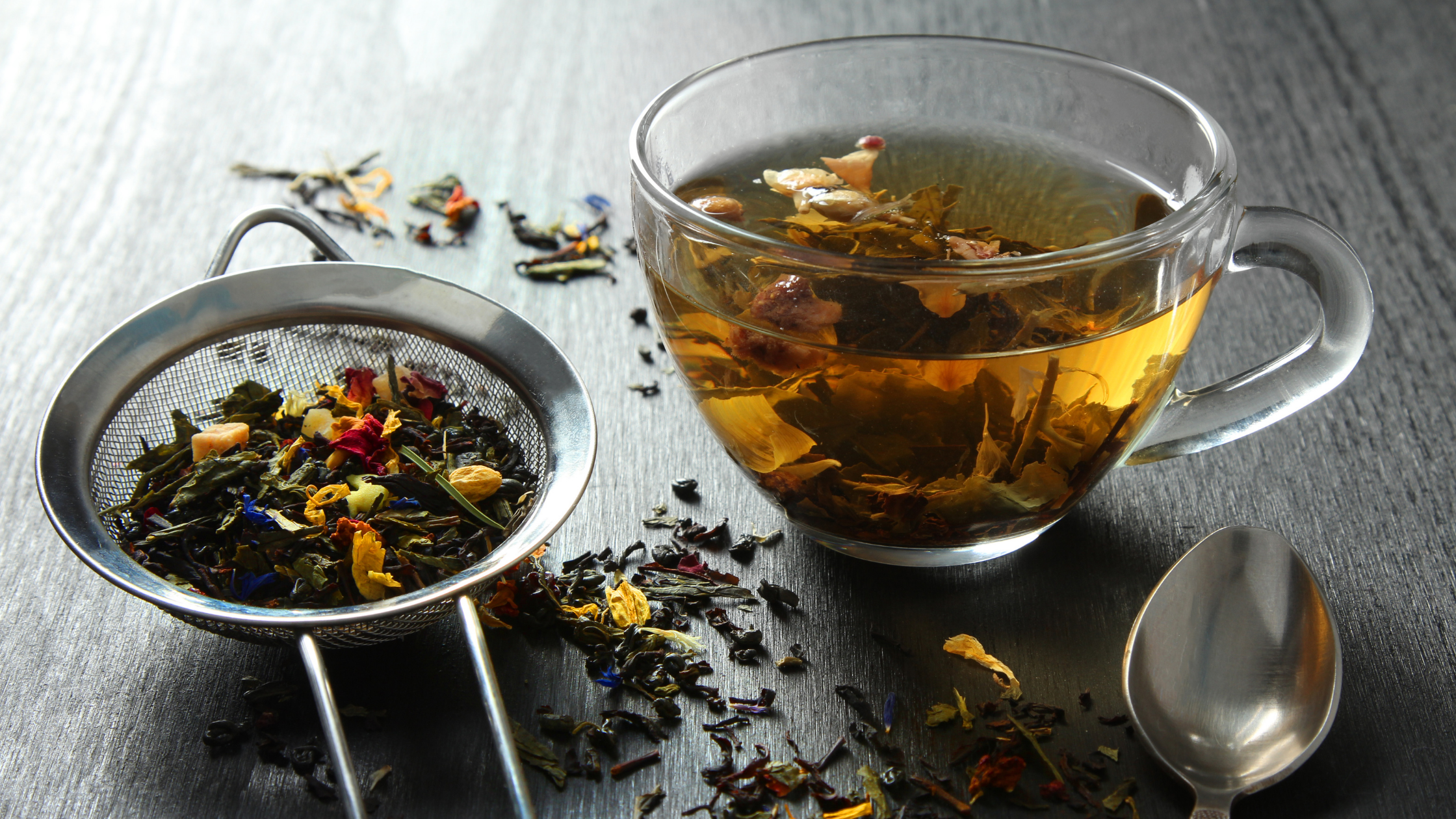 Glass cup with herbal tea in, popular galactagogues are in a metal strainer and scattered across a grey kitchen surface.