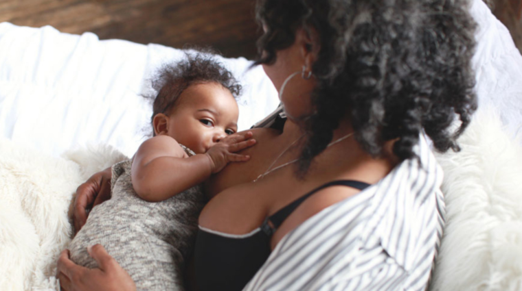 Close up of nursing dyad relaxing on a sofa. Mother wears a black vest top and striped shirt, she looks at her baby. Baby has its hand on her breast and looks at the camera.