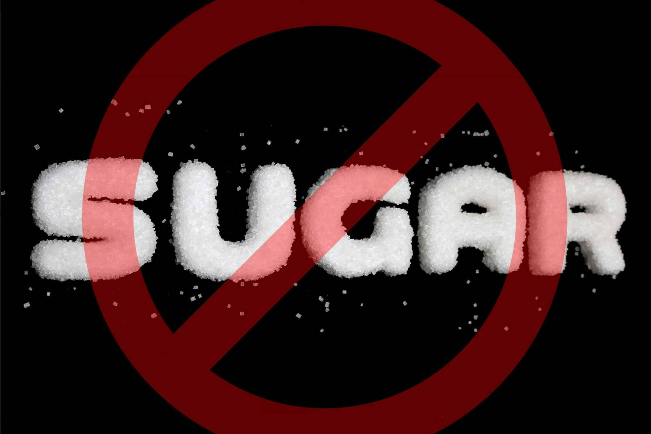 The word SUGAR spelled out in sugar crystals with a red o entry sign placed on top
