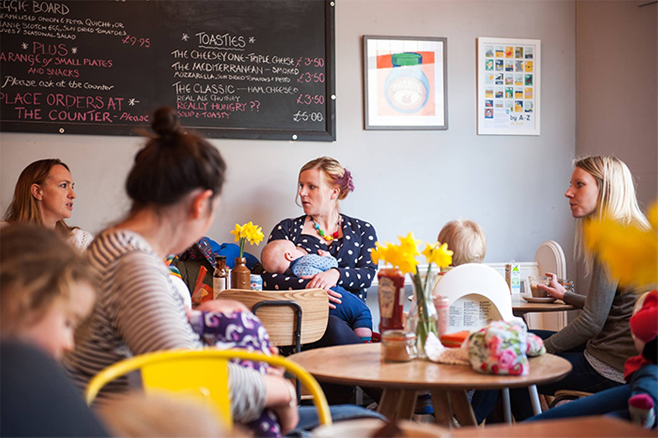 breastfeeding mothers sit in a cafe chatting, vases of yellow daffodils at the tables