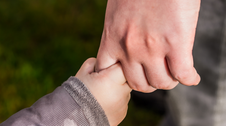 Adult's hand stretched down with child's chubby hand clasping the forefinger