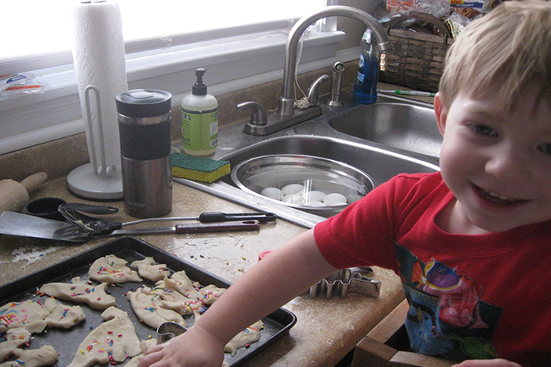 Smiling toddler stands at a busy kitchen surface his hand on an uncooked biscuit on the tray in front of him