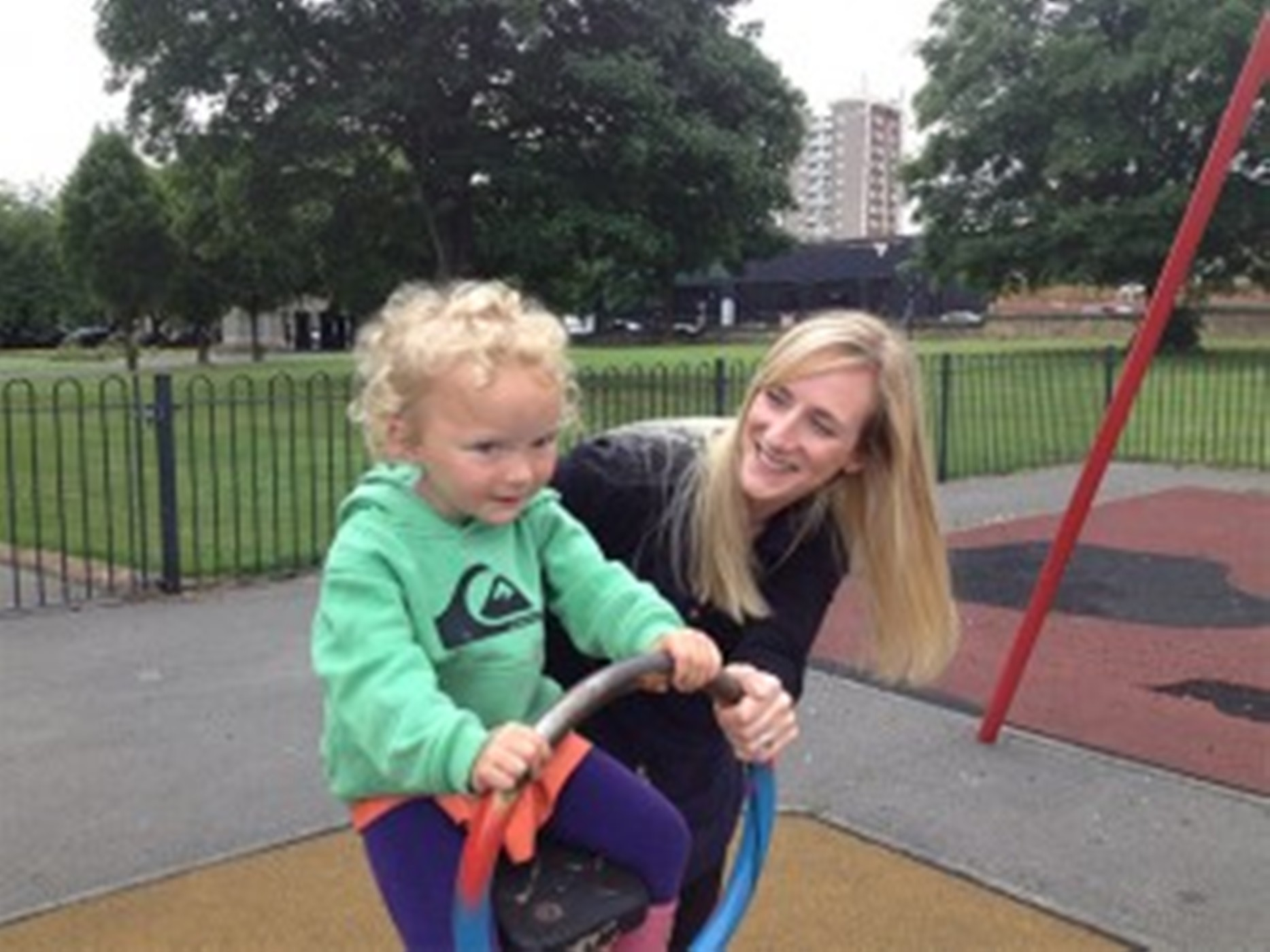 mother with toddler in playground, both smiling